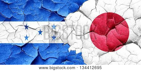 Honduras flag with Japan flag on a grunge cracked wall