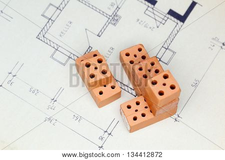 bricks on a blue print of a house