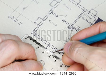 worker is drawing a blue print of a house