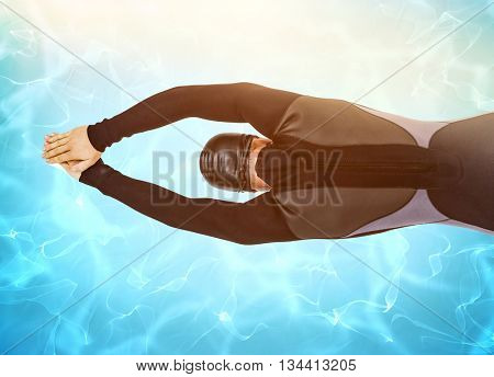 Rear view of swimmer in wetsuit while diving against blue pool under bright light