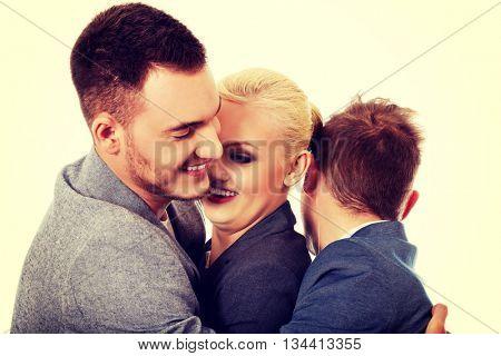 Happy group of three people hugging
