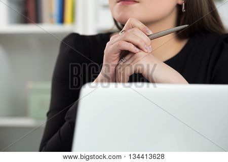 Close up view of woman sitting at laptop holding pen and thinking of something or listening to someone. Education seminar or blog writing concept.