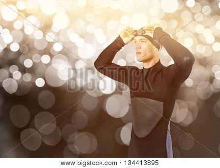 Swimmer in wetsuit wearing swimming goggles against glowing background