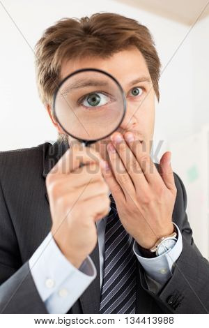 Funny business man holding magnifying glass portrait. Private detective investigation layer crime business research or security concept