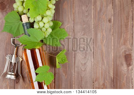 Bunch of grapes, white wine bottle and corkscrew on wooden table background with copy space