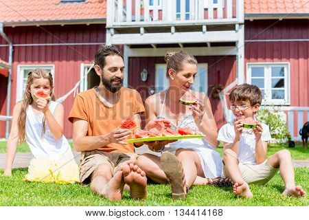 Family sitting in grass front of home eating water melon