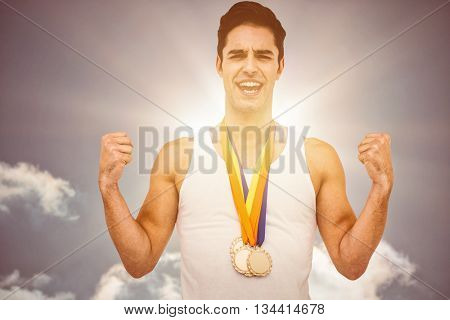 Athlete posing with gold medal after victory against sky