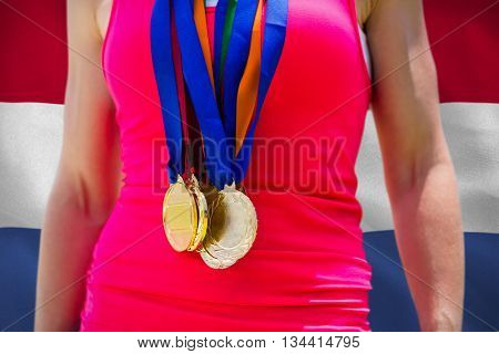 Portrait of sportswoman chest with medals against digitally generated netherlands national flag