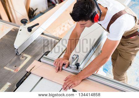 Carpenter or cabinet maker in his wood workshop