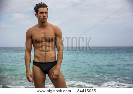 Attractive muscular young shirtless athletic man standing next to water by sea or ocean shore, wearing trunks or swimming suit, looking to a side in a cloudy summer day