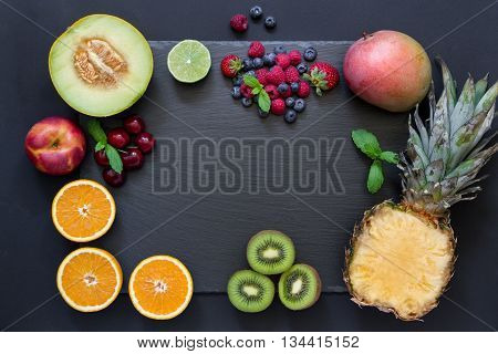 Rectangle of pineapple mango kiwi oranges lime melon nectarine and cherries strawberries blueberries raspberries in center empty space on black background. Fruits berries rectangle. Horizontal.