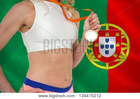 Athlete holding gold medal after victory against digitally generated portugese national flag