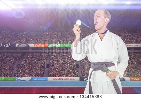 Fighter holding gold medal and screaming against composite image of playing field with supporter