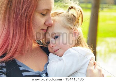 Mother and daughter portrait hug kissing in a park outdoor