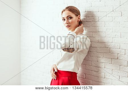 Portrait of a smilling stylish woman posing in white studio