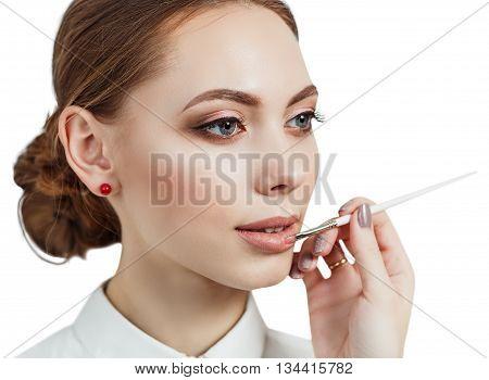 Hand of visagiste applying lipstick on female lips isolated on white