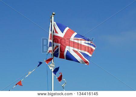 Union Jack flag flies on flagpole with bunting