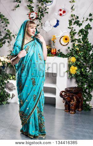 Pregnant blonde woman posing in blue indian sari