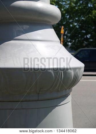 Closeup of marble column base against city street abd trees