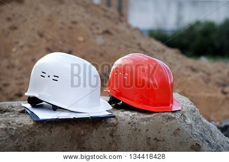 Orange helmet builder and a white helmet engineer. Helmets lie on a concrete block on a background of mountains of sand