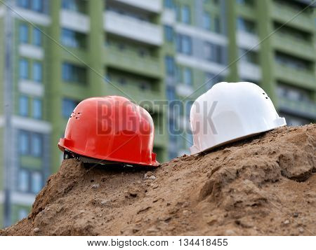Orange helmet builder and a white helmet engineer on the background buildings. Helmets are a mountain of sand