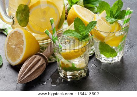 Lemonade pitcher and glasses with lemon, mint and ice on stone table