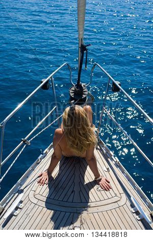 Beautiful female tanning on the yacht, active lifestyle, back side of sexy tanned woman body, luxury sea cruise, traveling and tourism concept