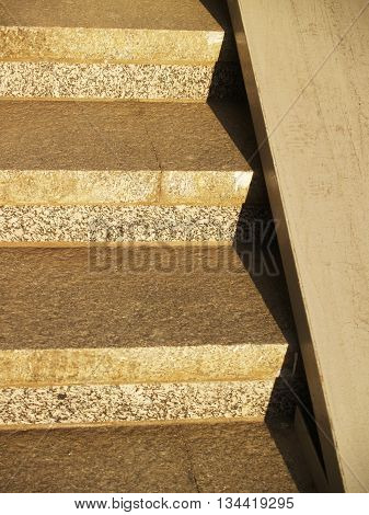 Detail of concrete stirway with metallic ramp sunlit