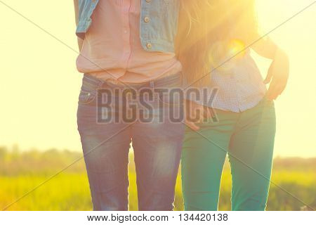 Happy Teenage girls in casual wear- jeans in sun light, outdoors. Unrecognizable Teenage girlfriends having fun together. Casual teen fashion clothes