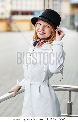 Beautiful woman in white coat on the city street