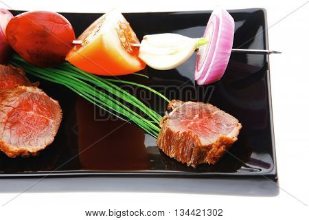 meat food : bbq meat served on black plate with vegetables on spit isolated on white background