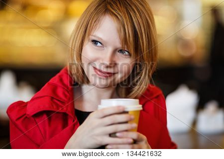 Woman drinking coffee indoors. Coffee to go. Close-up