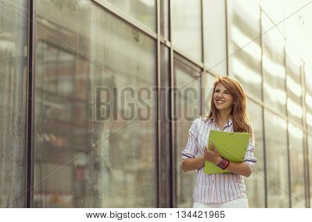Young beautiful business woman on a break walking next to an office building delighted