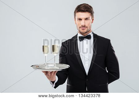 Handsome young butler in tuxedo holding tray with two glasses of champagne over white background