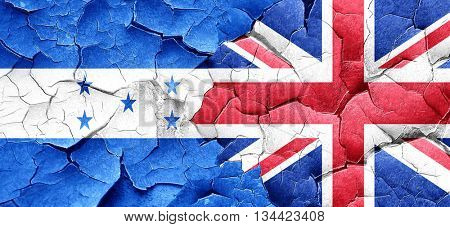 Honduras flag with Great Britain flag on a grunge cracked wall