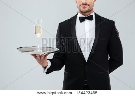 Handsome young waiter in tuxedo and bow tie standing and holding tray with glass of champagne over white background