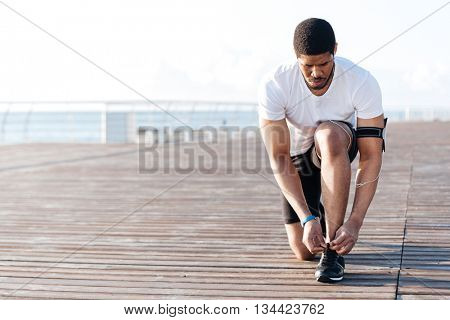 Serious african american young sportsman laces his sneakers on wooden terrace