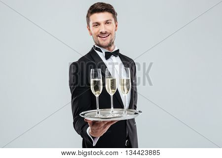 Cheerful young butler in tuxedo smiling and offering champagne over white background
