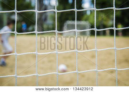 Beach soccer player through the net.