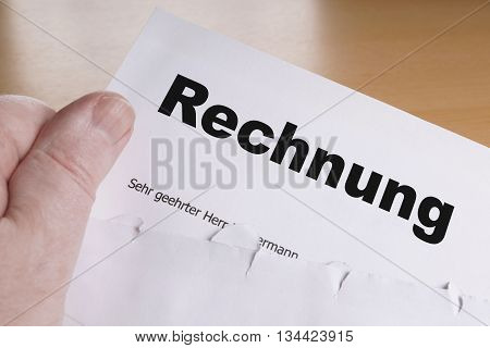 Rechnung hand holding german invoice letter with opened envelope