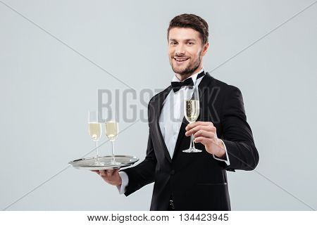 Happy young butler in tuxedo holding tray and glass of champagne over white background