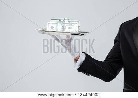 Closeup of tray with money holded by waiter hand in glove over white background