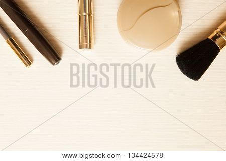 Golden Cosmetics - Mascara, Lipstick, Powder, Blusher, Brush Pencil On Light Wooden Background With