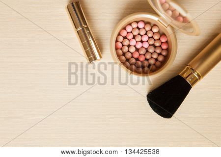 Golden Cosmetics - Lipstick, Powder, Blusher, Brush On Light Wooden Background With Copyspace. Top V