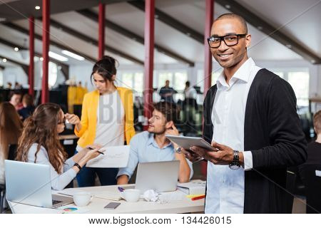 Cheerful african young businessman using tablet in office with colleagues on background