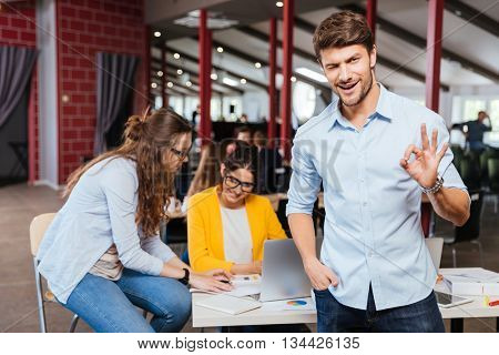 Happy successful young businessman standing and showing ok sign with his colleagues on background