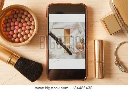 Smartphone With Glamour Insta Photo And Golden Cosmetics - Lipstick, Powder, Blusher, Brush, Perfume