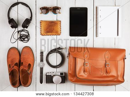 Travel concept - tablet pc headphones camera shoes watch and bag on the desk
