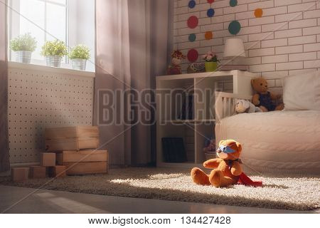 Interior of colorful bedroom for child. Toy teddy bear in a super hero costume.