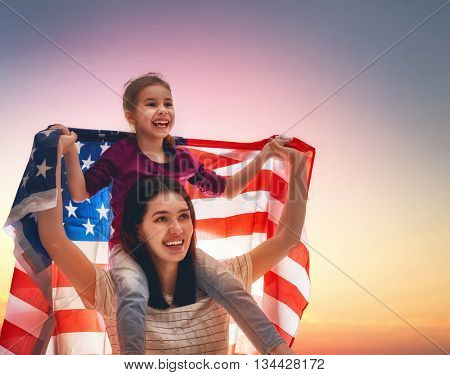 Patriotic holiday. Happy family, mother and her daughter child girl with American flag outdoors. USA celebrate 4th of July.